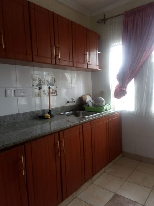 a well spacious kitchen with a fridge, cooker, utensils and enough cabinets for our guests.