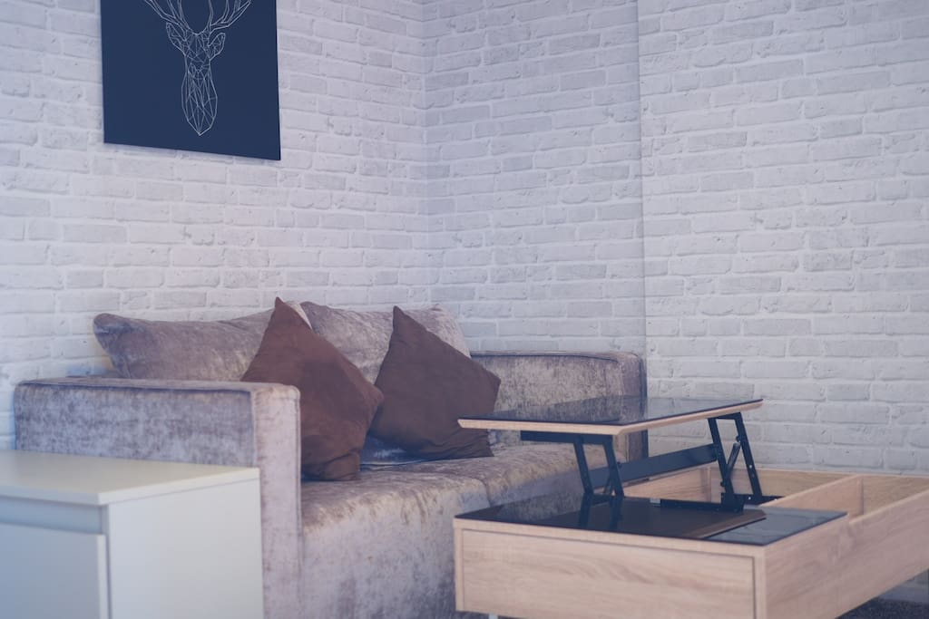 The living room is decorated in an elegant urban style with 2 seated brown sofa, a square white side table and rectangular coffee table which features a useful folding panel for your laptop.
