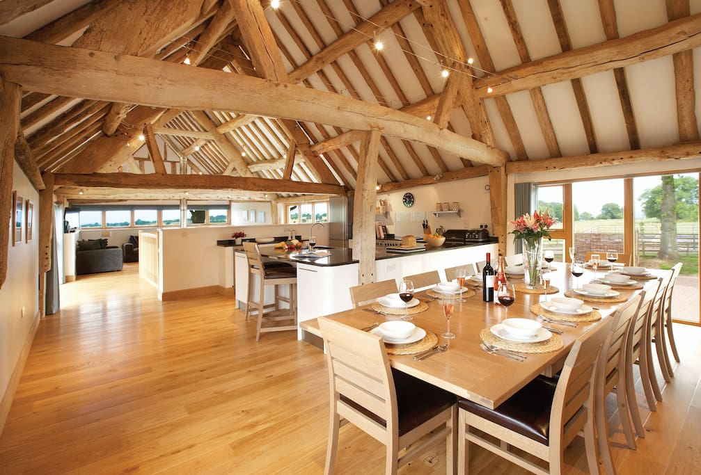 First floor Main Barn: Sitting room with wood burning stove, open plan kitchen and dining area that seats up to 14 guests