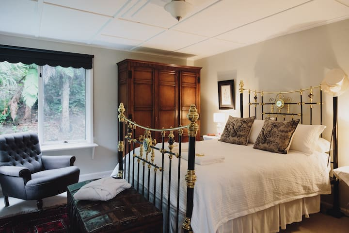 Master bedroom with Victorian brass bed and solid oak cupboard.