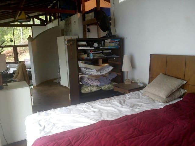 Vista do interior da casa a partir da cama de casal, a direita fica o quarto menor e depois a entrada para o banheiro e ao fundo a cozinha