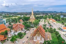 Wat Chalong. Well worth a visit. Go up to the top of the tower to the viewing deck and get some great photos, with  panoramic views . There are some shops that sell trinkets and Thai hand crafts , which make great gifts for the folks back home.