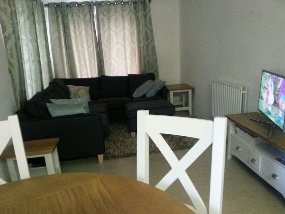 Corner sofa, dining table and television.