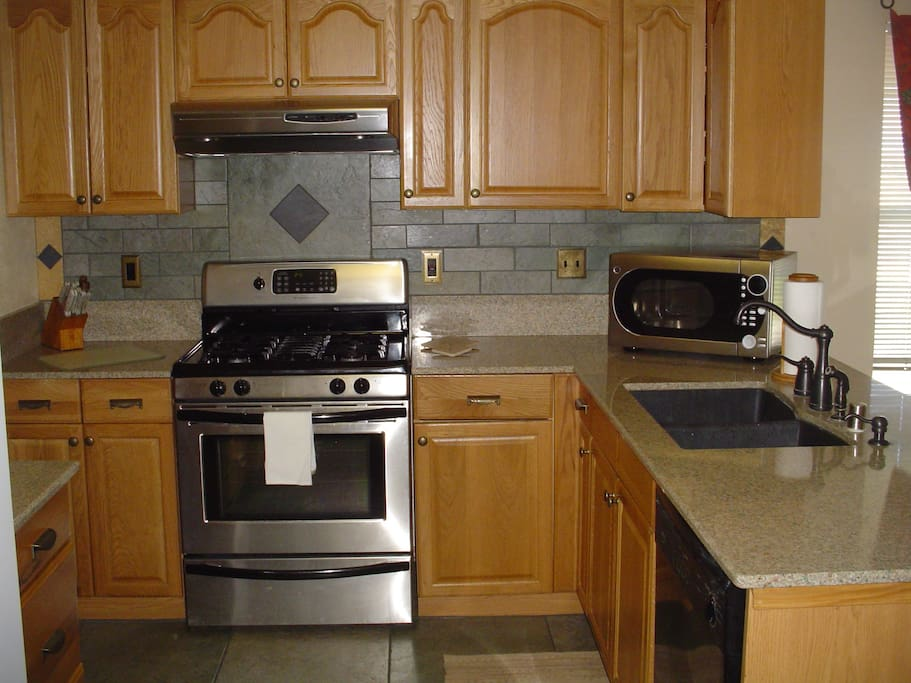 Kitchen with all appliances, dishes and utensils.