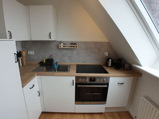 Küche mit Herd, Geschirrspüler und Kühlschrank
