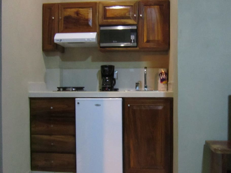Small kitchen with all appliances that are need, coffee maker, blender, dishes, pots, pans, etc.