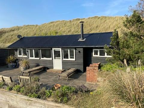 Lodge i sandklitter ved siden af stranden