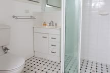 A clean, bright bathroom with a heater on the wall. We provide a hairdryer.