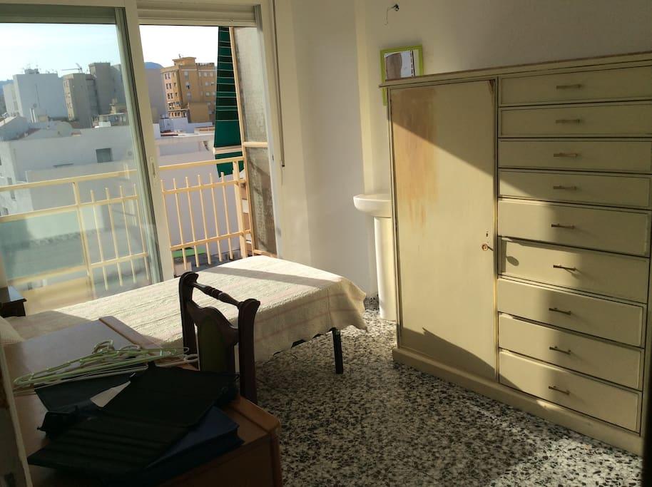 Dormitorio con balcón privado y lavabo.