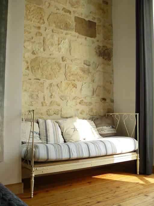 Des pierres et poutres apparentes, un canapé en fer forgé : telle est l'ambiance de la chambre.
