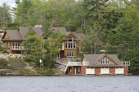 Picture perfect 5+ bed custom built cottage & boathouse on Lake Muskoka. 4,620+ sq ft, soaring ceilings & picturesque SW view. Exquisite Great Room with floor to ceiling Muskoka Stone Fireplace &  3 slip boathouse. Motorboat available for a fee.