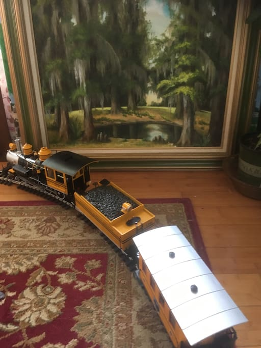 Toy train set around dining table.  Artists studio.  Many paintings
