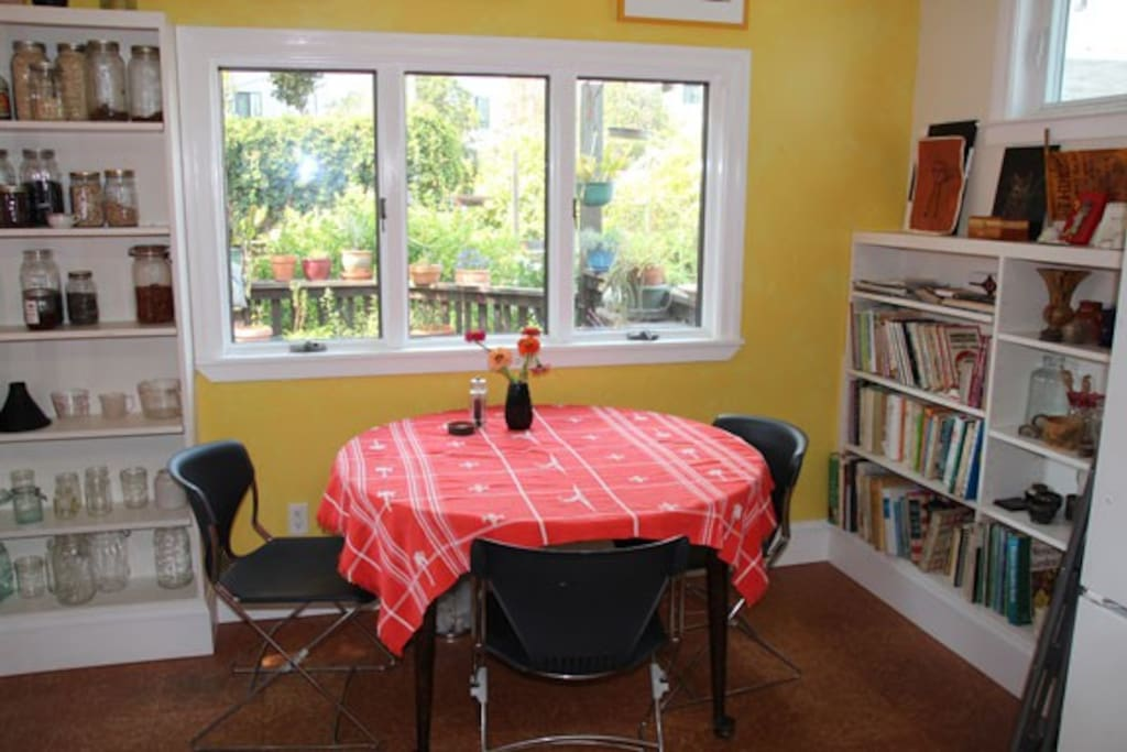 A breakfast nook looks out to the deck, garden, and bird feeders.