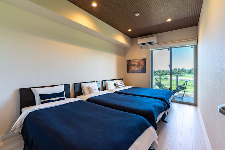 There is a double bed 1, 2 single beds and a large closet. Outside the window is a brown sugar field, on the left side of which the sea is spreading.寝室2、ダブルベッド1、シングルベッド2、大きなクローゼットがあります。窓の外はウージー畑、その左側には海が広がっています。
