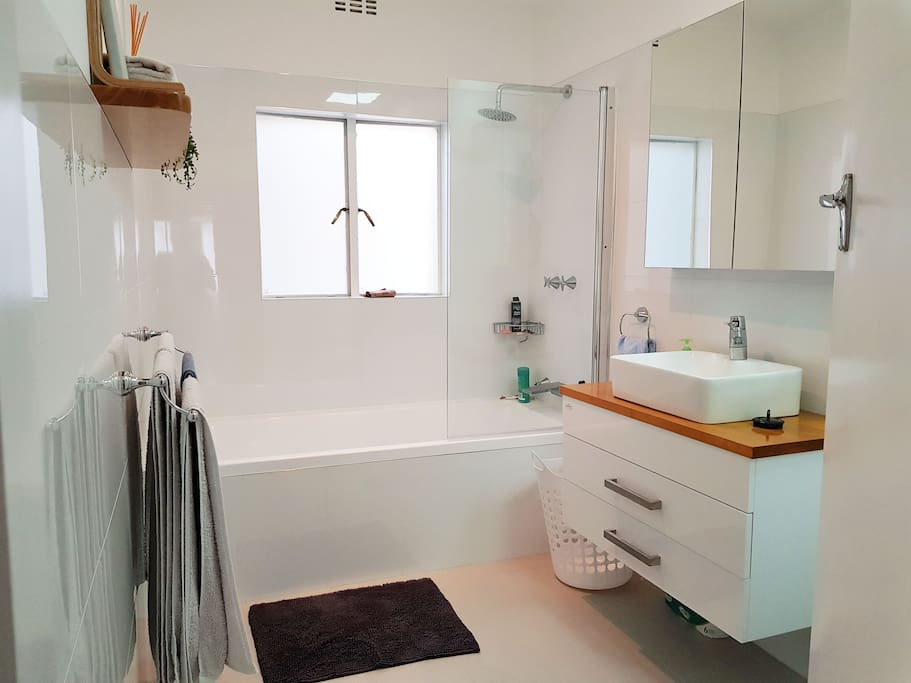 Bathroom with deep bath, shower overhead and plenty of storage space