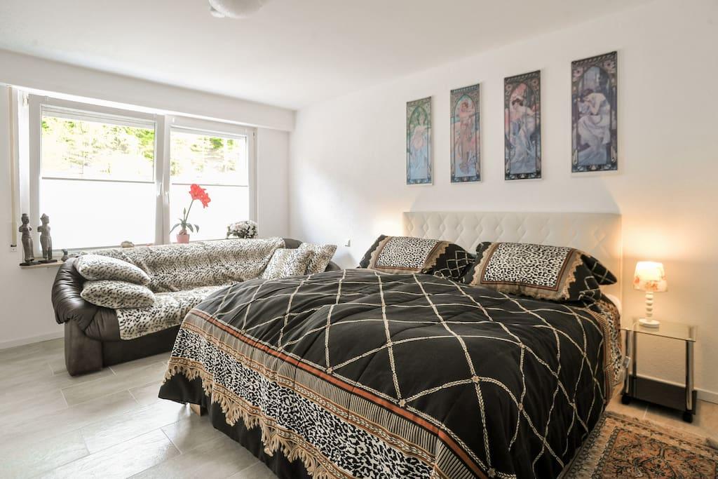 Grosses Schlafzimmer mit Flachbildfernseher und Sitzgelegenheit.