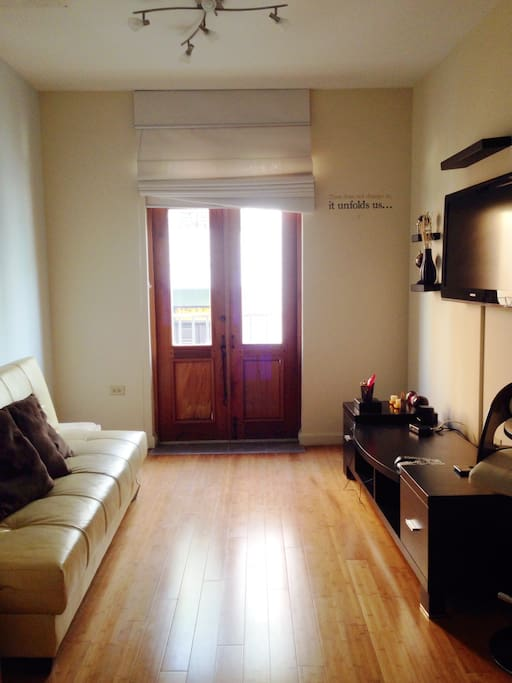 Bright living/dining area with access to balcony, separate AC unit in living area.