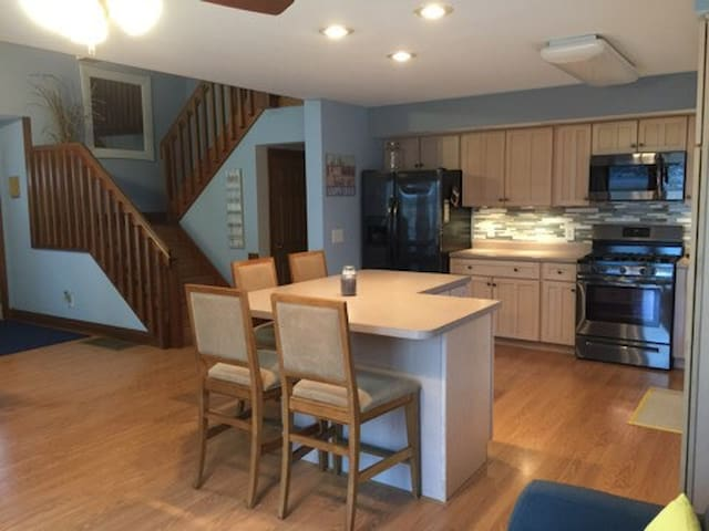 Kitchen area with 4 person seating around island. Kitchen fully stocked with Keurig machine, coffee pot, pots/pans,  plates, glasses, and utensils.