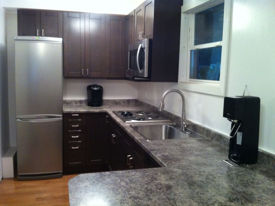 Kitchen with large microwave, cooktop, dishwasher coffee maker. everything needed for two to stay comfortably.