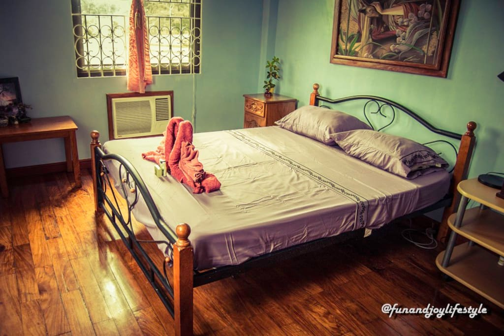 Room with air conditioner and queen-size bed with a view of a rice field on the 2nd floor.  Clean linen, bath towels, face towels, shampoo, conditioner and soap are provided.