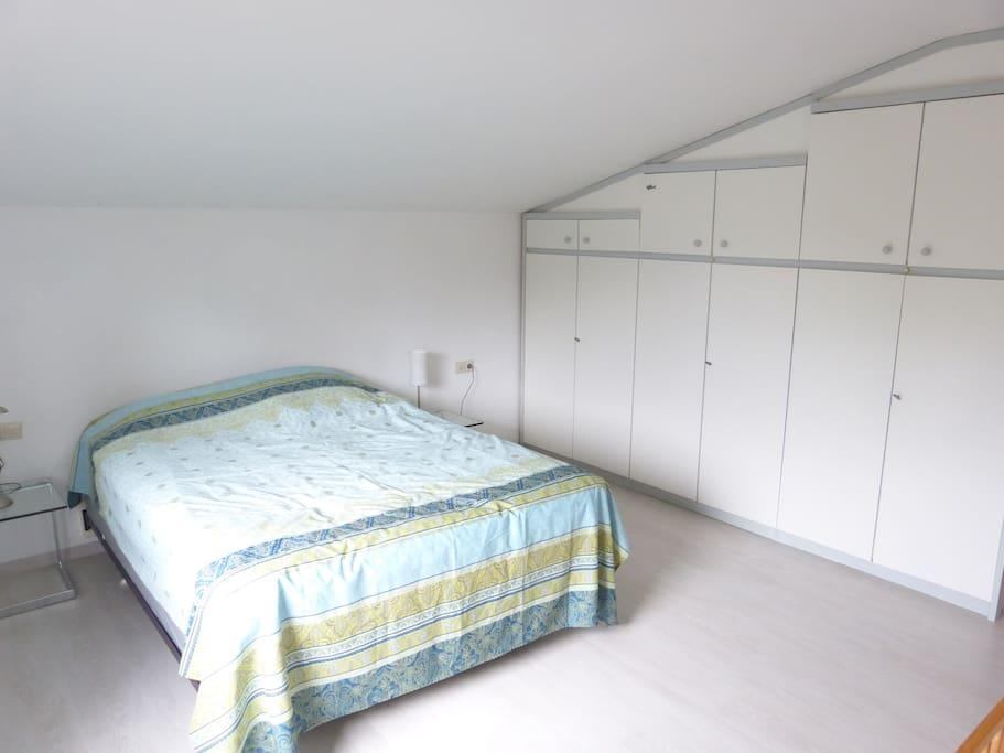 Schlafzimmer mit Queensizebett und gräumigem Einbauschrank