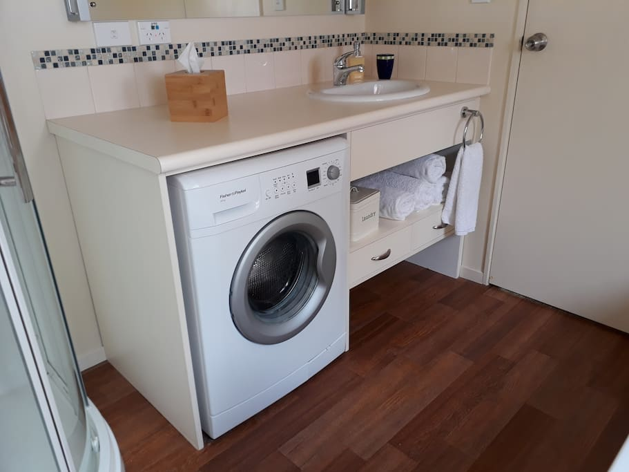The bathroom also has a front loader washing machine