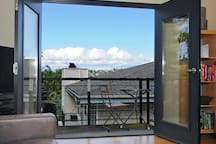 Balcony view of the Olympic mountains, Queen Anne Greenbelt, and nearby territorial views of Magnolia and Ballard neighborhoods.