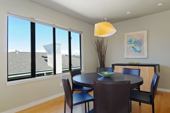 Dining area seats up to six comfortably at round table.   Tall windows look out on to the Olympic mountains.  From this space, you can see some beautiful Seattle sunsets!