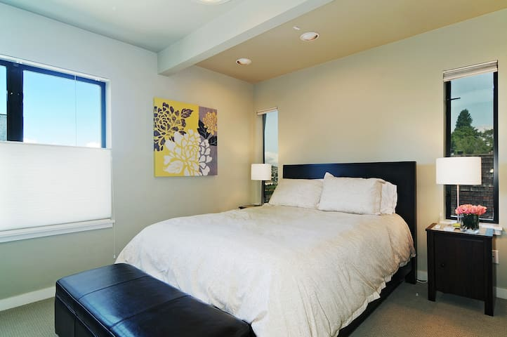 Spacious bedroom with queen size bed.   This room has a large wall of closet space.   Bed linens provided as well as additional blankets if needed for those cooler days & nights.
