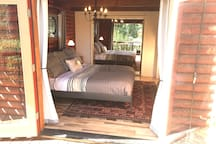 Downstairs king bedroom with French doors to peaceful deck