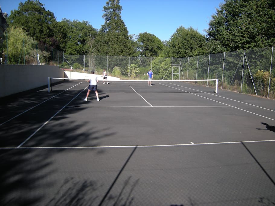 Full-size fenced hard surface tennis court