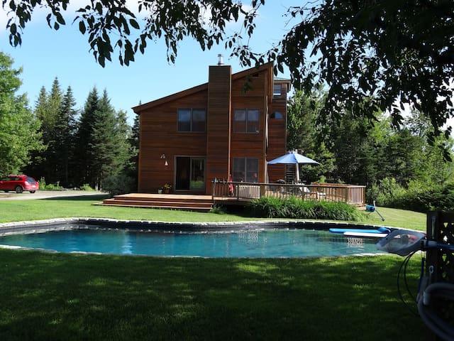 In summer, dine al fresco on the huge wrap-around deck or swim or laze around  stone-surround pool.