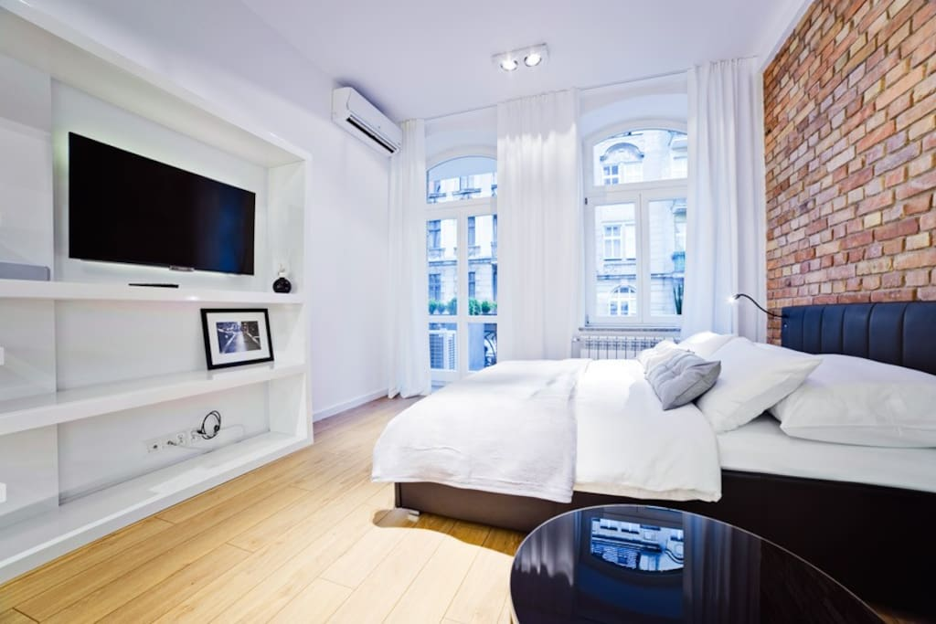 bed, tv, entrance to balcony