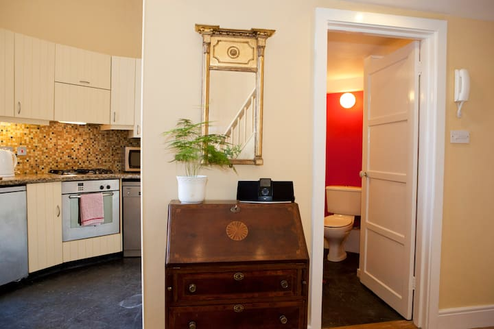 Antique bureau and Regency pier mirror flanked by kitchen and bathroom