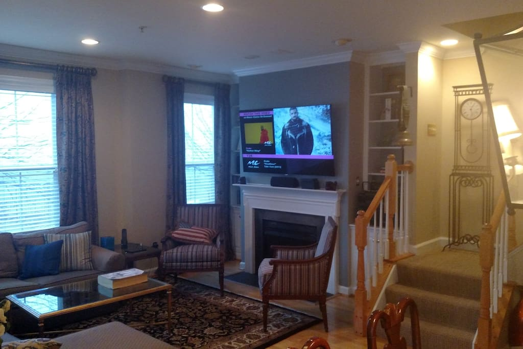 The living room has a 65 4K TV with surround sound and a working fireplace.