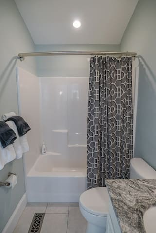 Bathroom with shower tub and single vanity.