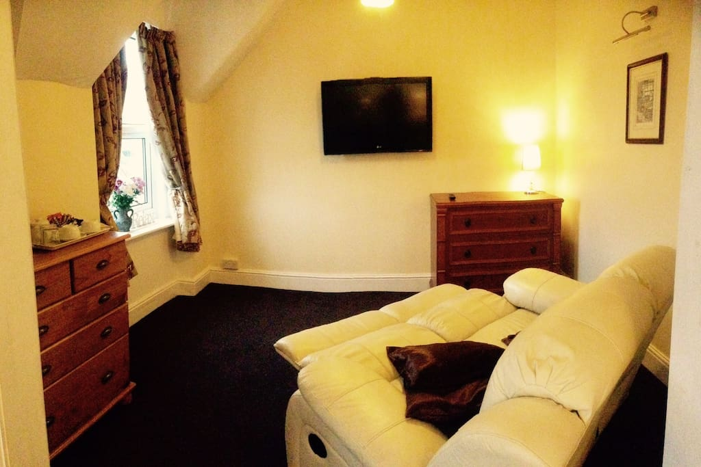 Room has got a lounge with reclining sofa and 40 inch TV