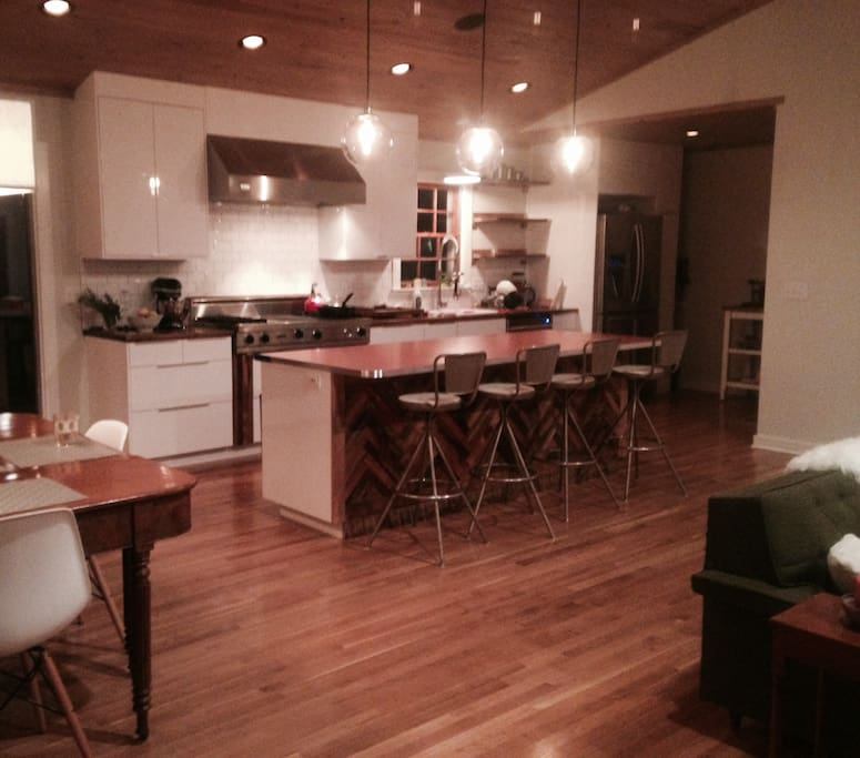Our kitchen,  living, and dining areas feature an open floor plan that has french doors that open to a deck.