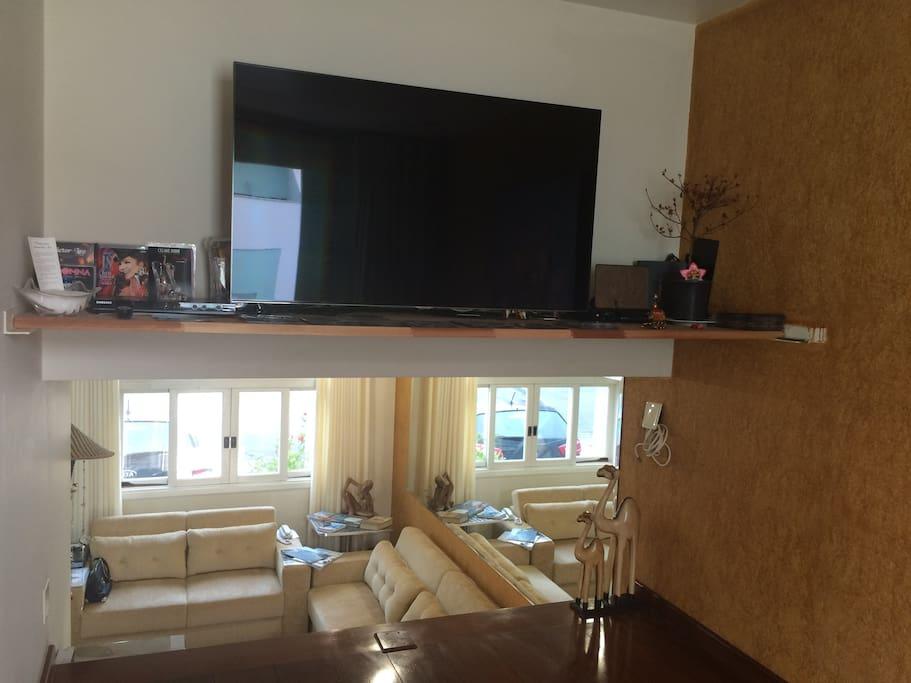 Sala de TV com vista para sala de estar e janela da fachada da frente.