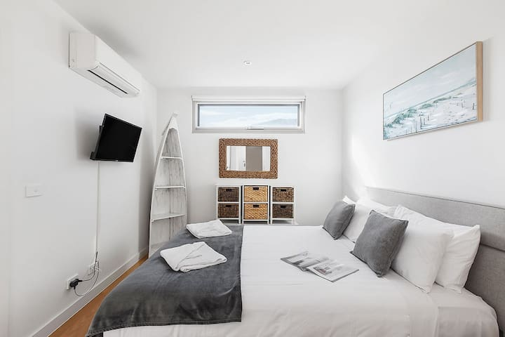 A main bedroom features a queen bed, built-in wardrobes, coastal decor, air conditioning, a wall-mounted TV, and direct access to the only bathroom.