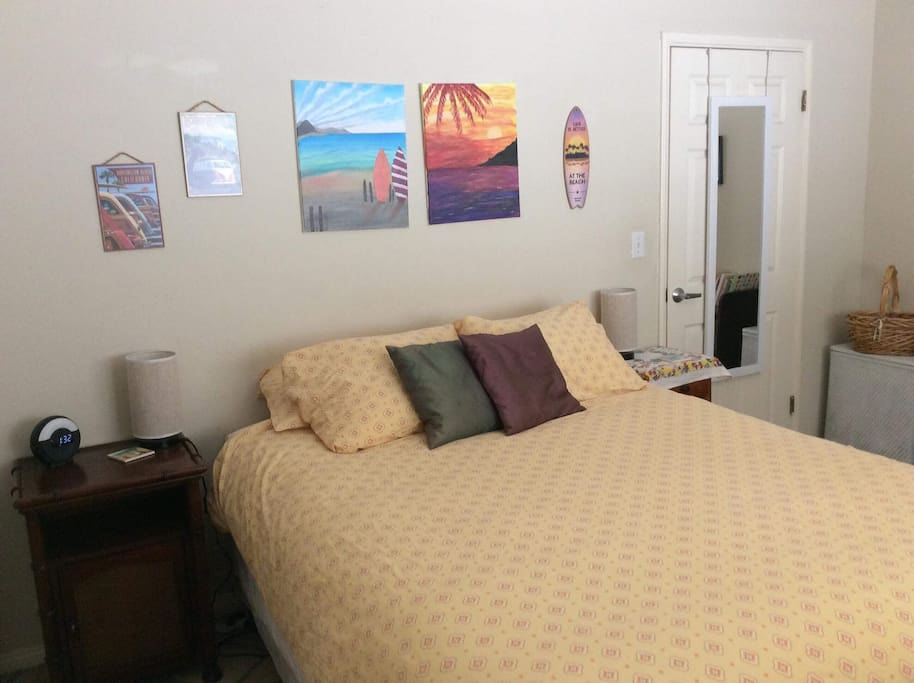 Private bedroom with queen bed, armoire dresser, closet, desk, luggage rack, TV and ceiling fan.