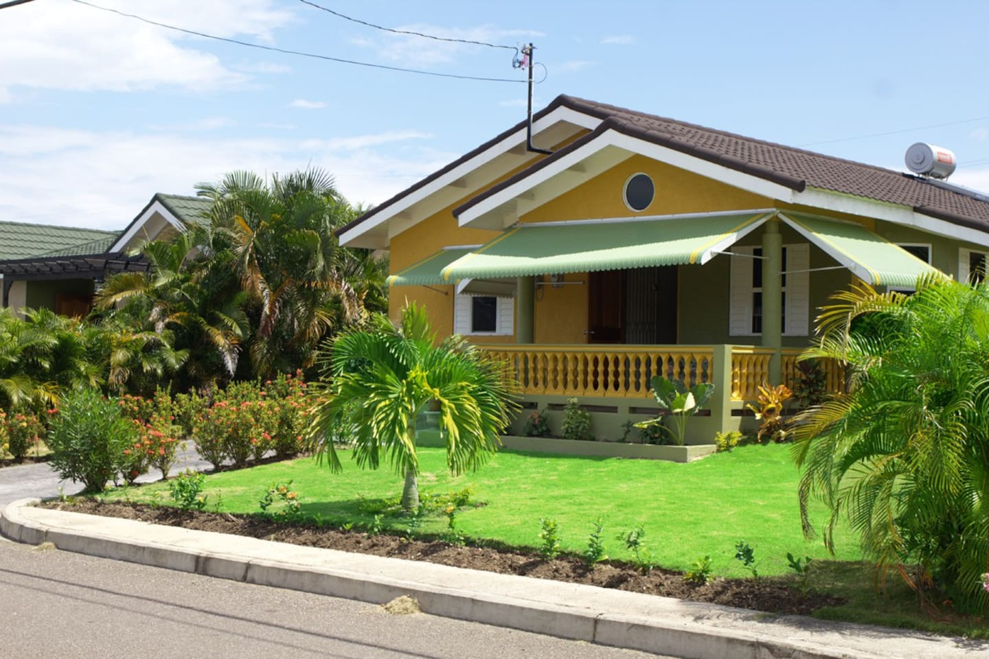 Frontal view of the Manor Vista - Cozy Ensuite with bright, blended colors  and thick palms on both sides; manicured lawn and beautiful flowers set in the back drop of a tropical  skyline
