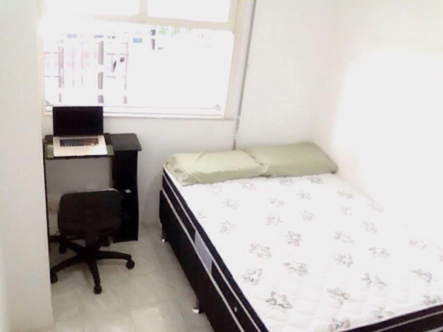 Quarto com cama de casal e escrivaninha