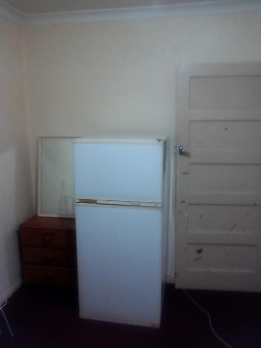 Fridge in room, draw and mirror.