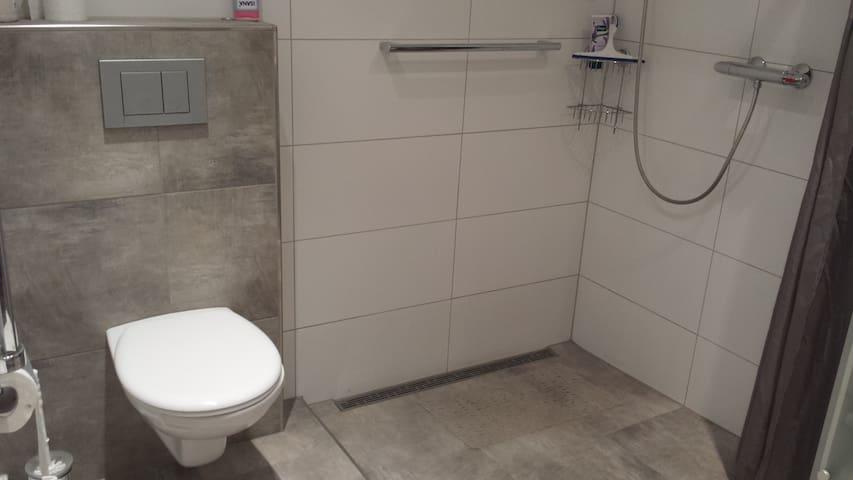 Im Badezimmer Toilette mit großzügiger, ebenerdiger Dusche