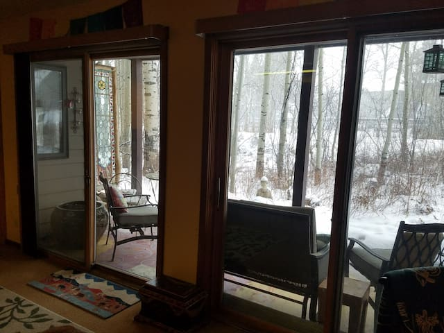 Double sliding doors open to a patio and aspen trees between the dining and living areas.