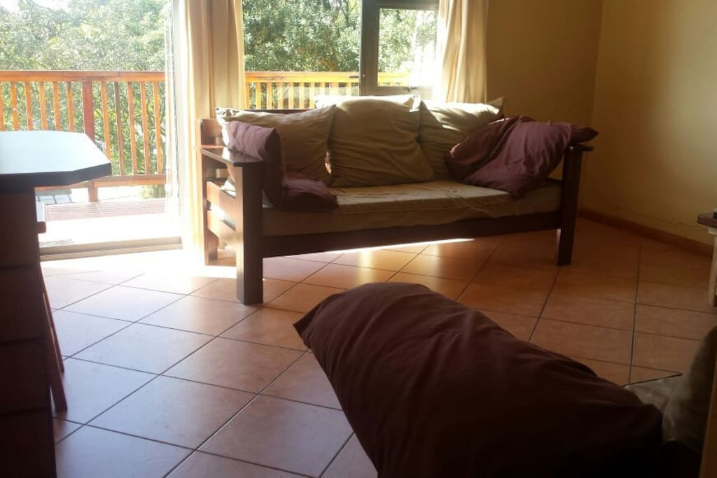 Table with chairs in kitchen area on left. Second single bed/couch and a bit of your view