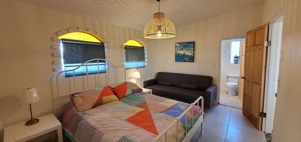 Two master suites in house, this is the queen bedroom with ensuite.  Dos recamaras principales en la casa, esta es la recamara con cama queen al fondo su baño propio.