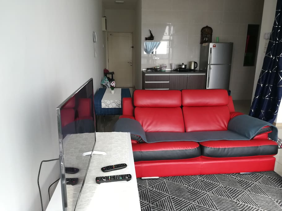 Living room with comfortable couch, air-conditioning, fan, desk, television with Astro channel.