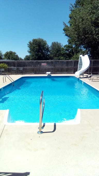 In ground pool with diving board and slide